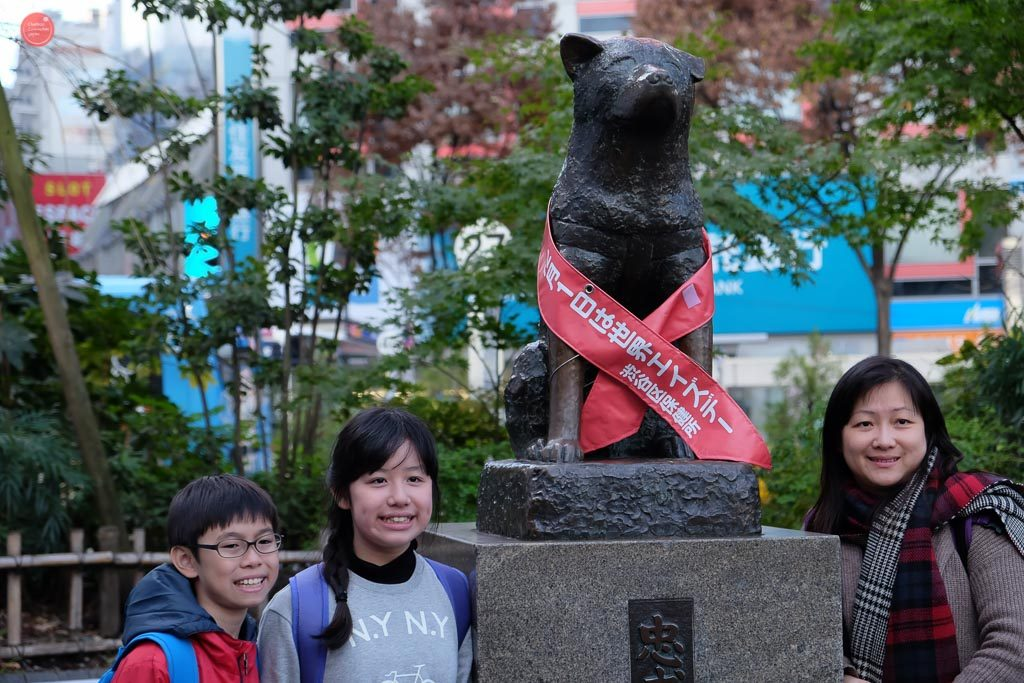 Tourists line up to have a picture taken with Hachiko's monument.